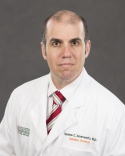 doctor  Abramowitz, is wearing a white doctors coat with a white shirt and a red and white striped tie.